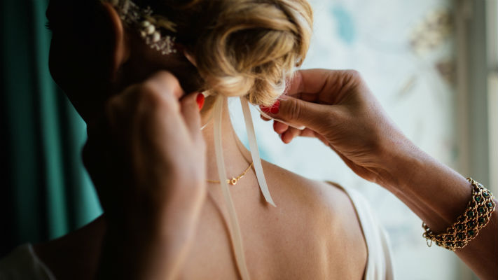 A close up of a ribbon being tied to a bride's hair