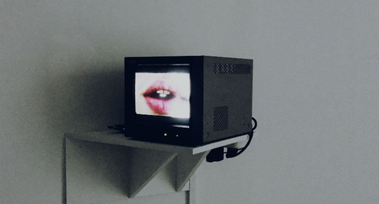 an image of a small television set with a close up open mouth on screen