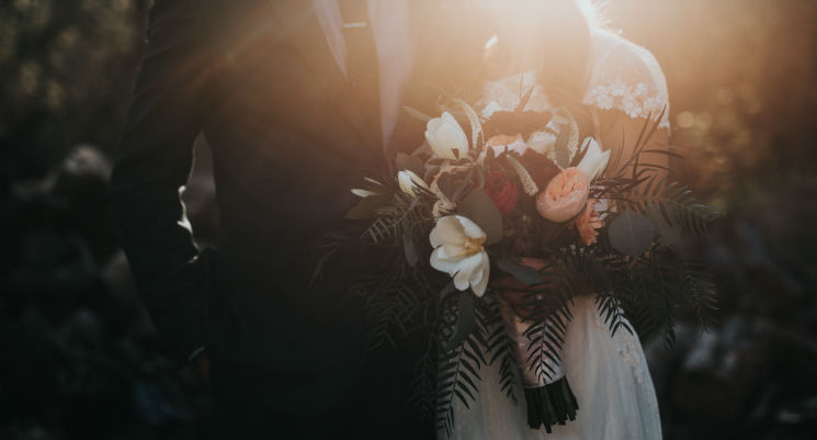 A bride and groom standing side by side withe the focus on the large bouquet of flowers