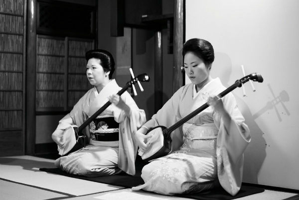 Two women wearing traditional Japanese dress playing the Shamisen instrument